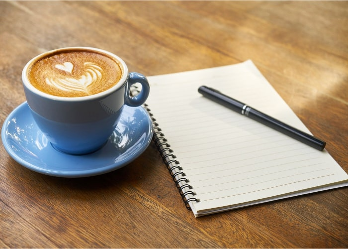 taza de cafe al lado de una libreta